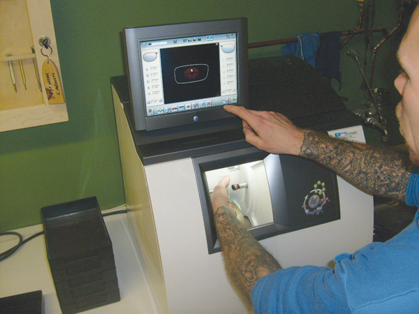 Photo of an offender using machinery to cut a glass lens for eyewear.