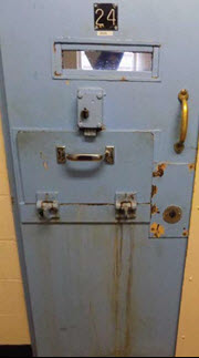 Photo of a rusting segregation cell door.