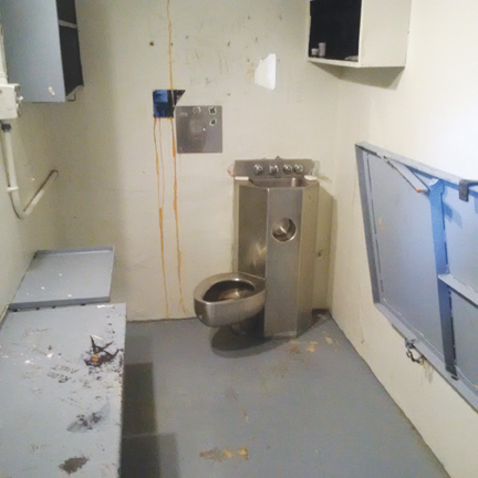 Photo of damaged cell from Saskatchewan Penitentiary riot.  Description follows.