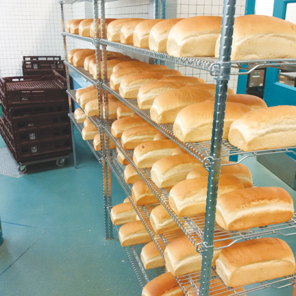 Photo of shelves of freshly baked loaves of bread.