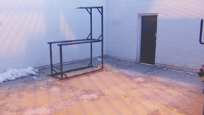 Photo of outdoor exercise yard showing concrete walls and metal bars.