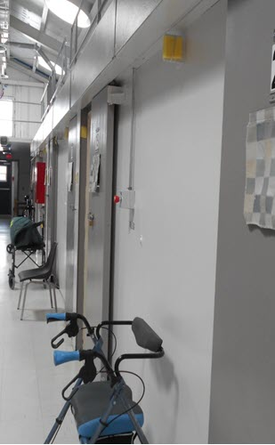 A picture of the range for older offenders at the Federal Training Centre.  The picture depicts a walker and a wheelchair in front of cell doors.
